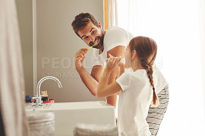 Buy stock photo Cropped shot of a handsome young man and his little daughter brushing their teeth in the bathroom