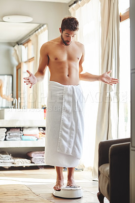 Buy stock photo Full length shot of a young man looking surprised while weighing himself in his bathroom at home