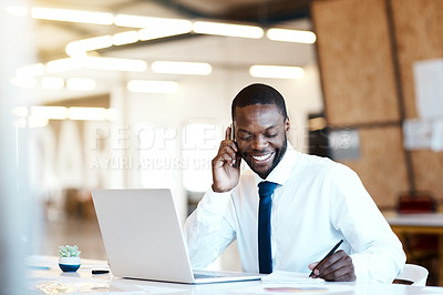 Buy stock photo Shot of a cheerful young businessman talking on his cellphone and making notes while being seated at his desk in the office during the day