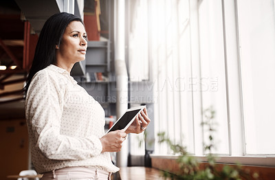 Buy stock photo Shot of a mature businesswoman using a digital tablet in an office