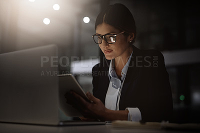 Buy stock photo Shot of a young businesswoman using a digital tablet and laptop during a late at night in a modern office