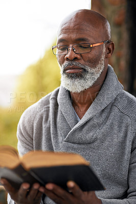 Buy stock photo Cropped shot of a handsome senior man reading his bible while sitting outside
