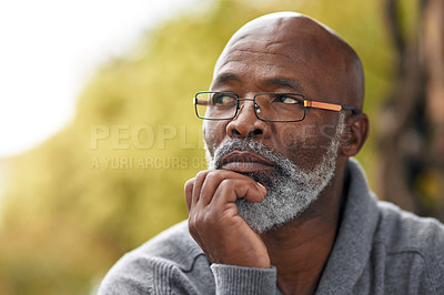 Buy stock photo Cropped shot of a handsome senior man looking thoughtful while sitting outside