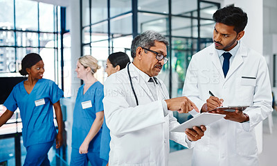 Buy stock photo Shot of two medical practitioners using a digital tablet together in a busy hospital