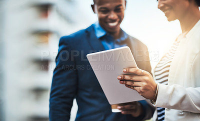 Buy stock photo Shot of two businesspeople using a digital tablet in the city