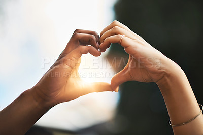 Buy stock photo Cropped shot of a couple making a heart gesture with their hands outdoors