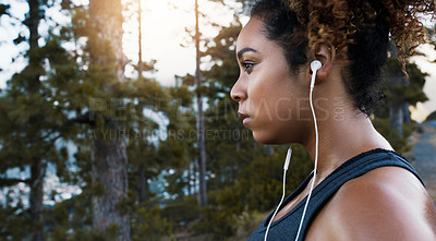 Buy stock photo Shot of a sporty young woman listening to music while exercising outdoors