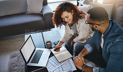 Buy stock photo Shot of a young couple planning their budget together at home