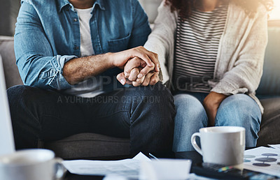 Buy stock photo Shot of an unrecognizable couple holding hands while planning their budget together at home