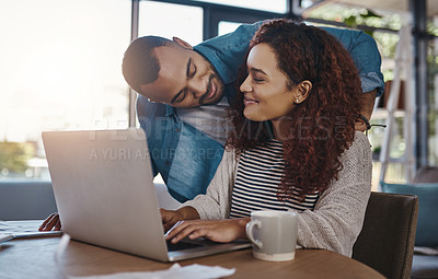 Buy stock photo Shot of a young couple planning their budget together on a laptop at home