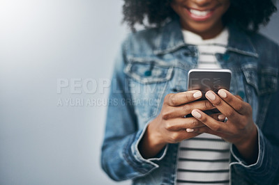 Buy stock photo Studio shot of an unrecognizable young woman using her cellphone against a grey background