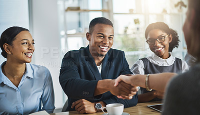Buy stock photo Cropped shot of two young businesspeople shaking hands during a meeting in the boardroom