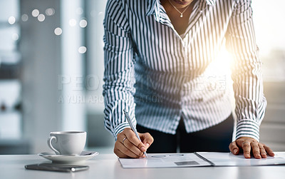Buy stock photo Closeup shot of an unrecognizable businesswoman writing notes on a document in an office