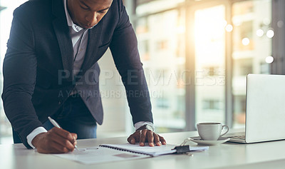 Buy stock photo Cropped shot of a young businessman taking notes while working in his modern office