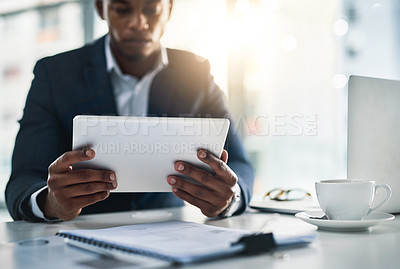 Buy stock photo Cropped shot of a young businessman working on his tablet in a modern office