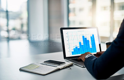 Buy stock photo Cropped shot of an unrecognizable young businessman working on his laptop in a modern office