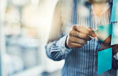 Buy stock photo Closeup shot of an unrecognizable businesswoman sticking adhesive notes onto a glass wall in an office