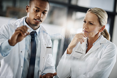 Buy stock photo Cropped shot of two scientists writing down formulas on a glass wipe board while doing research in their lab