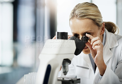 Buy stock photo Cropped shot of an attractive mature female scientist using a microscope while doing research in her lab