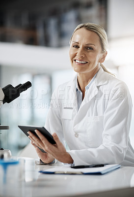 Buy stock photo Cropped portrait of an attractive mature female scientist using a tablet while doing research in her lab