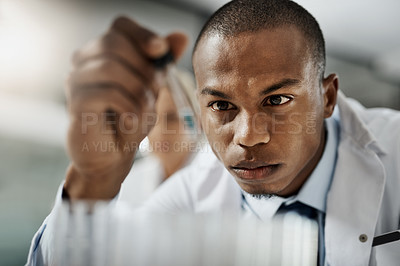 Buy stock photo Cropped shot of a handsome young male scientist testing a sample while doing research in his lab