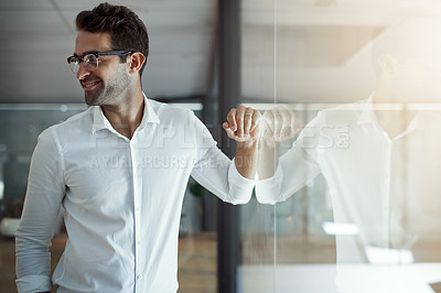Buy stock photo Cropped shot of a handsome young businessman leaning against a glass wall in his modern office