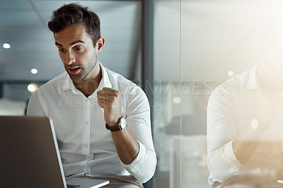 Buy stock photo Cropped shot of a handsome young businessman getting ready to cheer while working on his laptop in the office