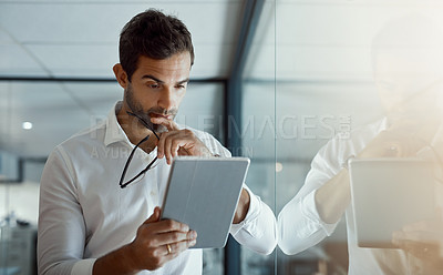 Buy stock photo Cropped shot of a handsome young businessman looking thoughtful while working on his digital tablet while standing in the office