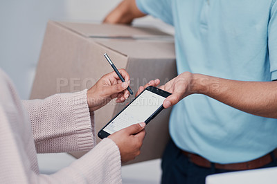 Buy stock photo Cropped shot of an unrecognizable man making a delivery and getting a signature from an unrecognizable female customer