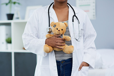 Buy stock photo Cropped shot of a female pediatrician holding a teddybear in her office