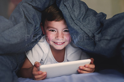 Buy stock photo Portrait of a little boy using a digital tablet while lying under a blanket in bed