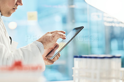 Buy stock photo Cropped shot of an unrecognizable young male scientist working on a tablet in his lab