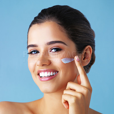 Buy stock photo Studio portrait of a beautiful young woman applying lotion to her face against a blue background