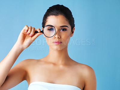 Buy stock photo Studio portrait of a beautiful young woman holding a magnifying glass against a blue background