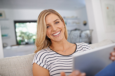 Buy stock photo Portrait of an attractive young woman using a tablet while relaxing on the sofa at home