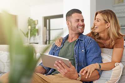 Buy stock photo Shot of an affectionate couple using a digital tablet while relaxing at home