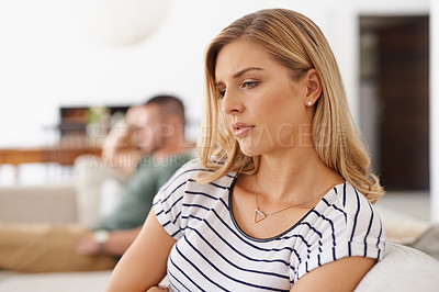 Buy stock photo Shot of an unhappy couple sitting apart from each other on a sofa after an argument at home
