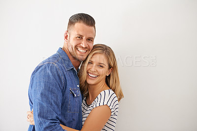 Buy stock photo Portrait of a happy and loving young couple embracing each other against a gray wall