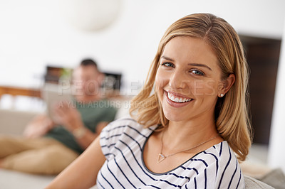 Buy stock photo Cropped shot of a young beautiful woman chilling on the sofa while her husband is in the background using a tablet in the living room at home