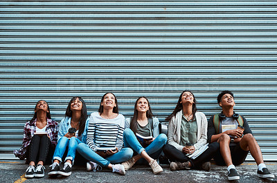 Buy stock photo Shot of a group of university students looking up while sitting outside at campus