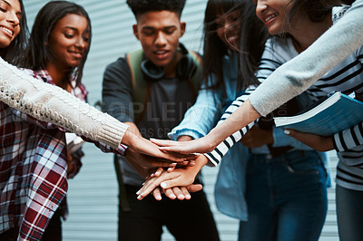 Buy stock photo Shot of a group of university students joining their hands together in a huddle at campus