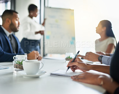Buy stock photo Cropped shot of an unrecognizable woman making notes while sitting in a meeting
