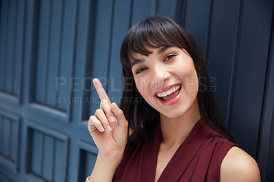 Buy stock photo Cropped shot of a young attractive businesswoman pointing at a empty space in a corridor at the office