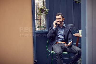 Buy stock photo Cropped shot of a young handsome businessman on a call at a cafe