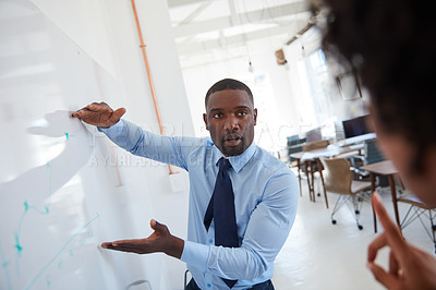 Buy stock photo Cropped shot of a young a businessman explaining information on a whiteboard to his female colleague in the office