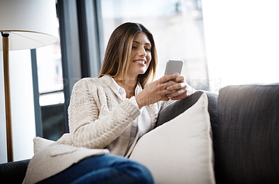 Buy stock photo Shot of a beautiful young woman using her cellphone while relaxing at home