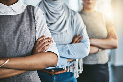 Buy stock photo Shot of a group of unrecognizable young businesswomen standing with their arms folded inside of the office at work