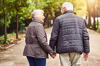 Buy stock photo Rearview shot of an affectionate senior couple out for a walk in the park