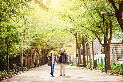Buy stock photo Full length shot of an affectionate senior couple out for a walk in the park