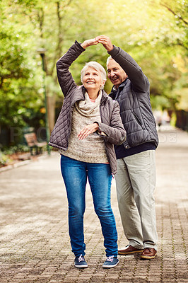 Buy stock photo Full length shot of an affectionate senior couple dancing in the park